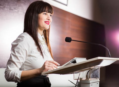 Pretty,,Young,Business,Woman,Giving,A,Presentation,In,A,Conference/meeting
