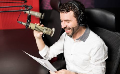 Smiling,Young,Male,Radio,Presenter,With,Headphones,Reading,A,Script